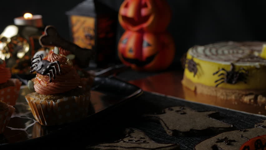Fancy Halloween food Party Table with Pumpkin Cupcake Muffin and cookies.   Shutterstock HD Video #1018135924