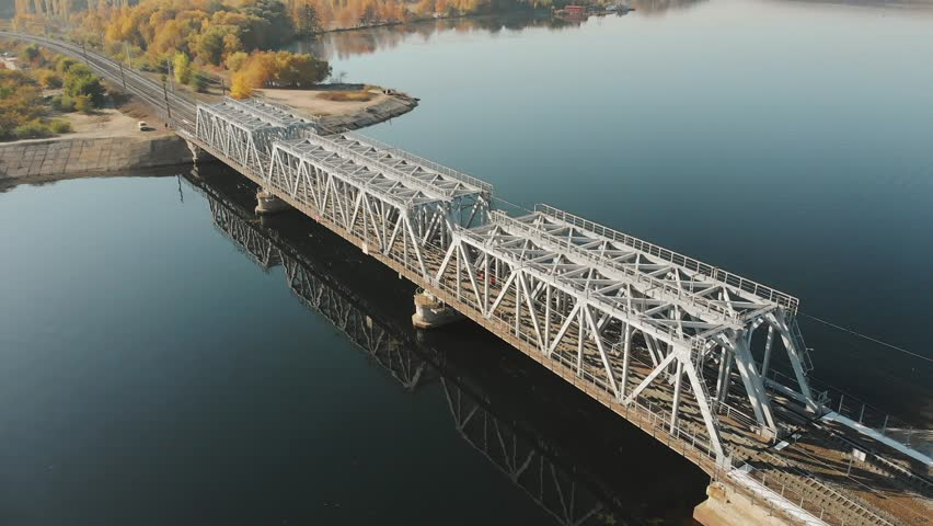 Aerial view drone shot of steel railroad bridge crossing big blue river, train transportation concept | Shutterstock HD Video #1018146004