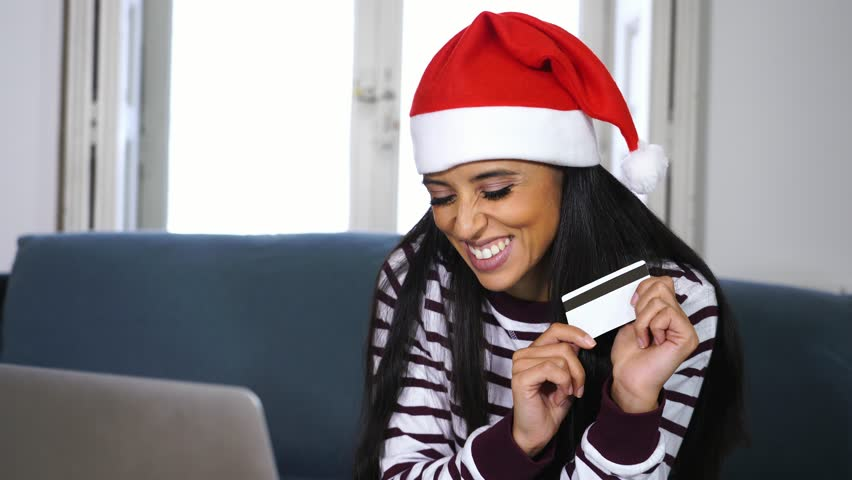 Woman wearing red sweater and santa claus hat choosing and buying christmas gifts online using a laptop sitting on a couch in the living room at home excited about having all ready for christmas. | Shutterstock HD Video #1018159474
