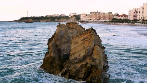 View on the most famous beach of Biarritz. In the foreground, there is a rock, next to the cliff. The sea is high and the waves hit the rock. Filmed in October.
