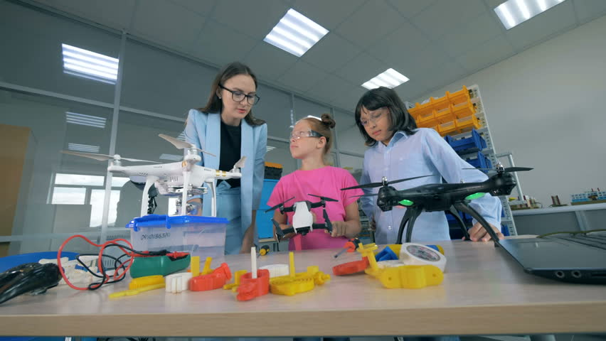 Two teenagers and a female engineer.are observing drones. 4K. | Shutterstock HD Video #1018188394