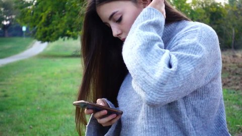 young teenage girl of 14 years writing messages on the phone chatting on social networks outdoors alone in a park