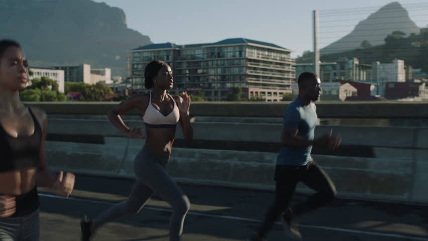 multi ethnic group athletes running friends enjoying competition race jogging exercising together focused on healthy fitness lifestyle in urban city at sunrise #1018213054