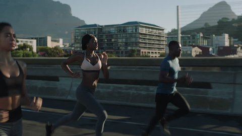 multi ethnic group athletes running friends enjoying competition race jogging exercising together focused on healthy fitness lifestyle in urban city at sunrise