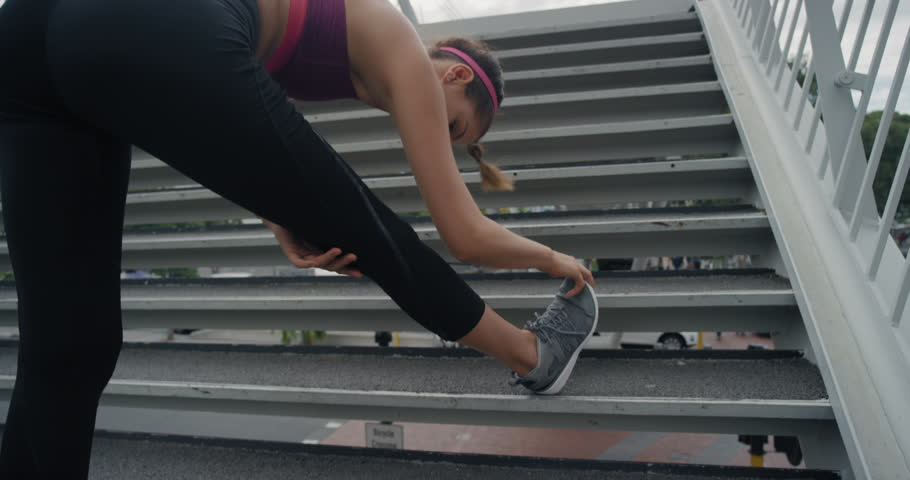 Athletic young woman runner stretching legs doing warm up exercise preparing for running workout in urban city | Shutterstock HD Video #1018214284