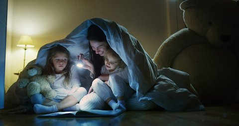 A mother tells stories to her daughters in the dark illuminating with a torch under the blanket. Concept: Love, Family, Dreams
