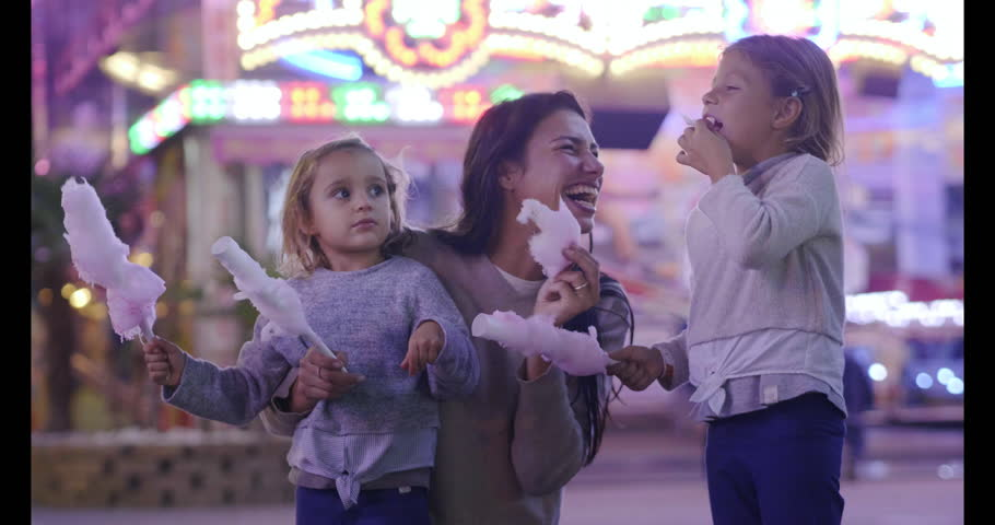 Portrait of a young mother having fun with her daughters at the Luna park. Concept: Family, happiness, freedom.