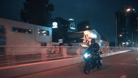 Bucharest, Romania-09.20.2018: Moving tracking shot driving riding suzuki gsxr motorcycle bike rider on a bridge night city street rolling skyline