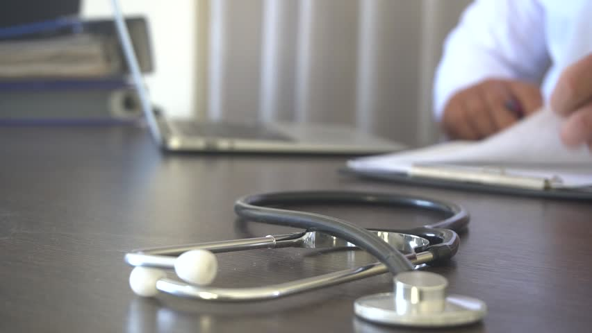 Doctor At His Desk Working On Paperwork Rack Focus To Document  | Shutterstock HD Video #1018315144
