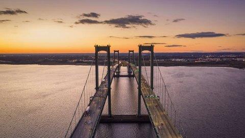 Aerial timelapse of Delaware Memorial Bridge at dusk. The Delaware Memorial Bridge is a set of twin suspension bridges crossing the Delaware River between the states of Delaware and New Jersey