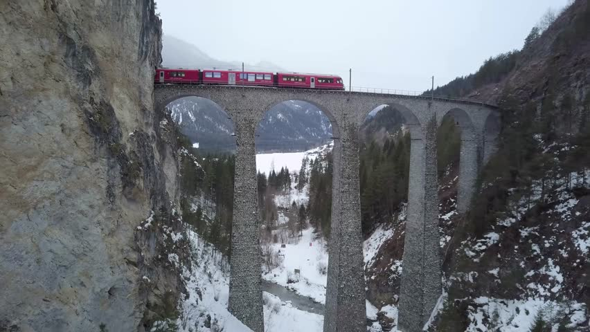 4K Aerial Drone view Landwasser Viaduct World Heritage Sight with Bernina Express in winter scenery in the Swiss Alps backwards fly through