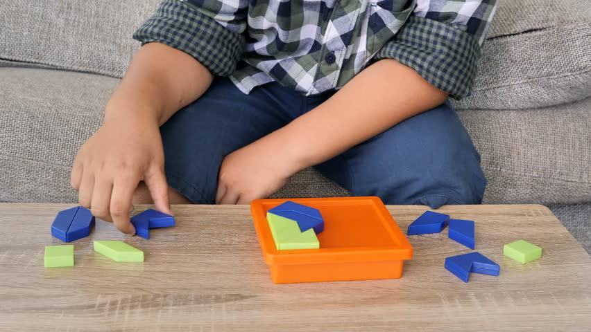 Boy asian children solving jigsaw puzzle on desk in the room. | Shutterstock HD Video #1018389604