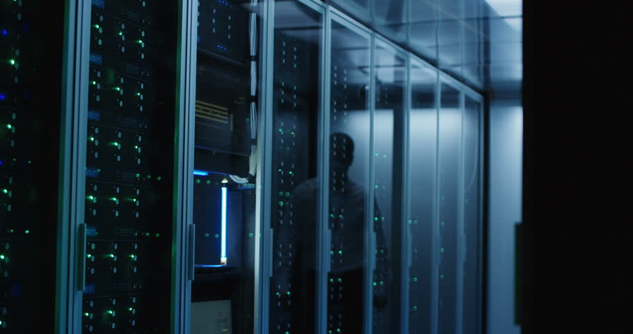 Medium shot of technician working on a laptop in a data center full of rack servers running diagnostics and maintenance on the system   Shutterstock HD Video #1018479394