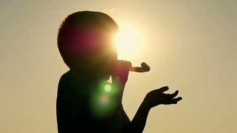 Silhouette of a happy child who blows a festive tongue-whistle. The boy plays with a whistle.