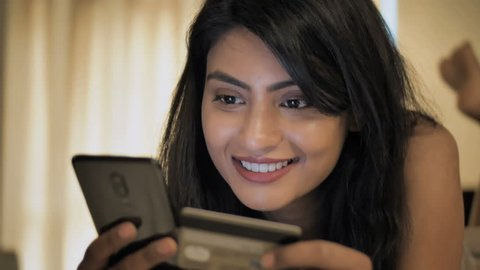 A happy and smiling woman making a card payment through mobile phone to pay bills. An attractive girl putting debit or credit card details on a smartphone or cellphone to make online transaction