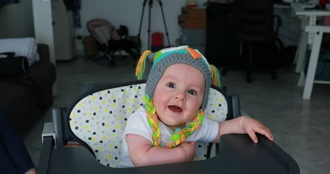 Beautiful Baby Boy With A Funny Colored Wool Hat On The Head, Cute Six Month Old Baby Boy In High Chair. Close Up View - DCi 4K Resolution