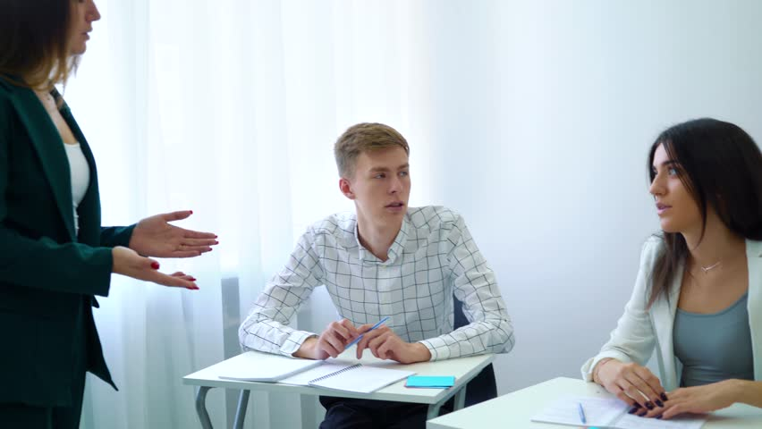 Young teacher discussing with students and training communication skills in classroom. interactive education, communication, knowledge, development, study concept | Shutterstock HD Video #1018577224