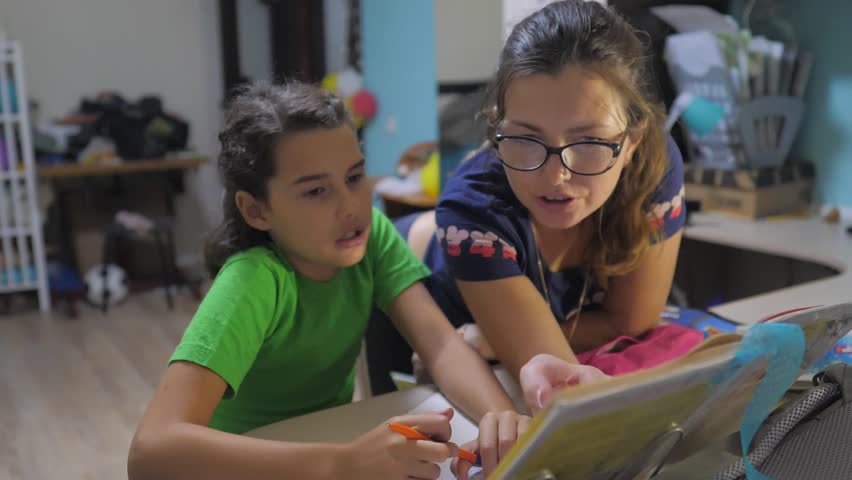 Mother and daughter do homework school. slow motion video. preparation, back to school. little girl and woman study with a book. school kids family lifestyle concept | Shutterstock HD Video #1018583584