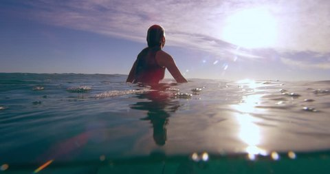Young female surfer sitting on surfboard in the ocean in Australian beach with bright day lighting soaking up the sun waiting for the next big wave. Medium shot on 4k RED camera.