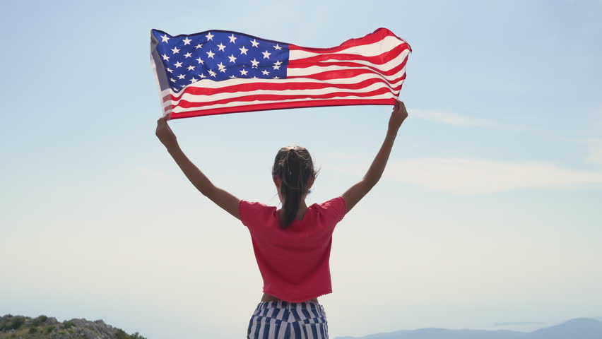 Child girl is waving American flag on top of mountain at sky background. 4K Footage | Shutterstock HD Video #1018698994