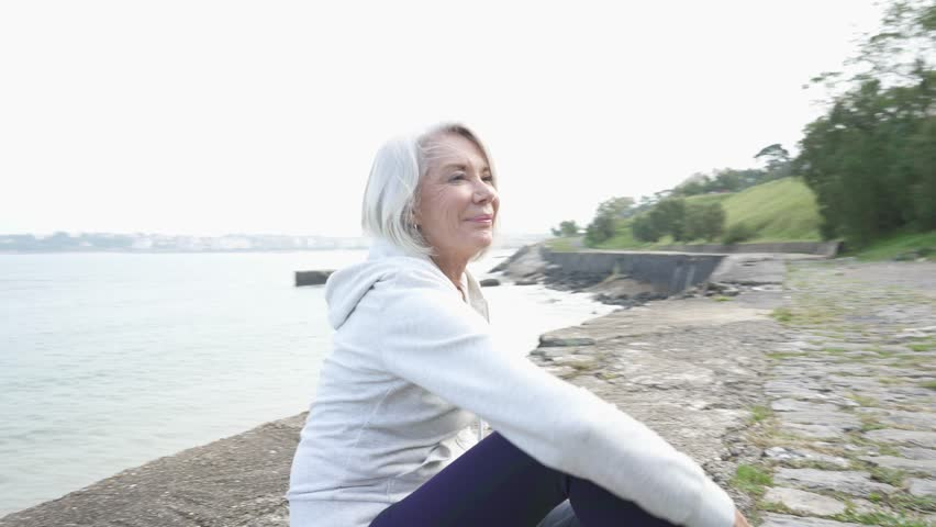 Beautiful elderly woman sitting by the ocean in sportswear                               #1018738144