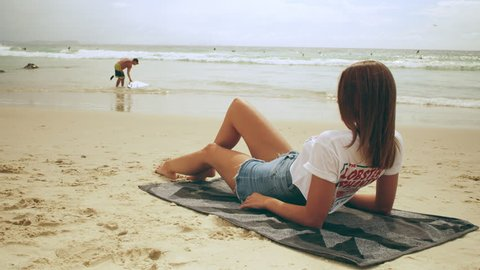 Beautiful young woman wearing cut off jean shorts and t-shirt lays on a towel on the beach on an Australian summer day. Medium shot on 4k RED camera.