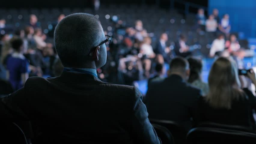 Official team works at crowded forum for collaboration or trading education. Modern concept of economic briefing for male partner or politician. Row of seats in large place for job worker or spectator   Shutterstock HD Video #1018763074