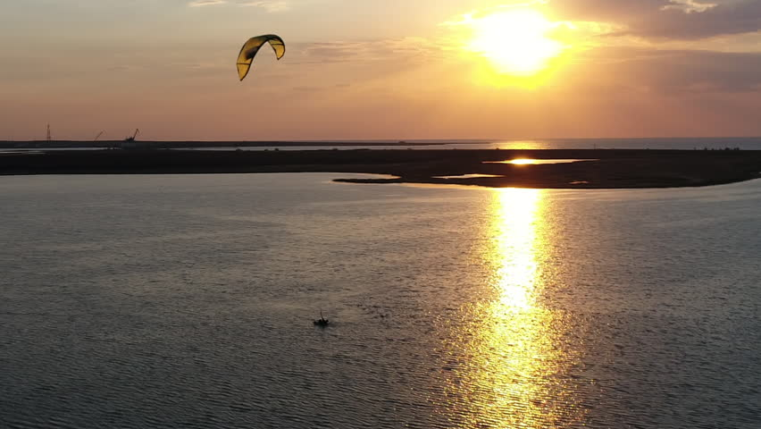 Riding a kite in the sunset. Silhouette of a man athlete on a kite-board in the sea, surfing on the board on the water surface follow the yellow wing. | Shutterstock HD Video #1018882564
