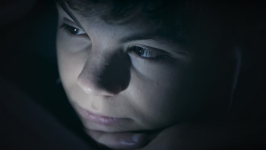 Boy watching movie or playing games on tablet computer at night. Child with headphones lying down under blanket on bed using smartphone or tablet pc. Boy to make video call to talk to friends.  | Shutterstock HD Video #1018965004