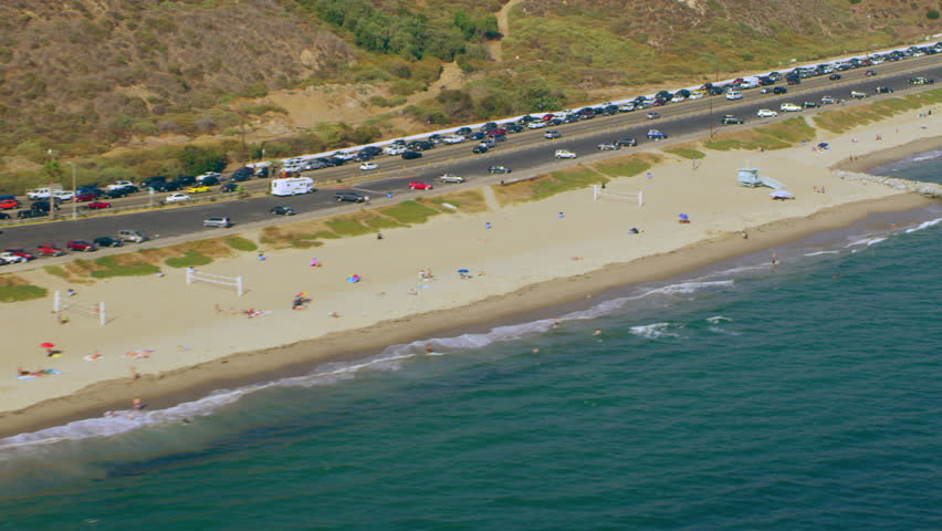 Aerial view of beach shoreline and PCH traffic on a sunny day in Los Angeles, California. Shot on 4K RED camera.