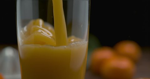 Orange juice being poured in a tall glass, on a wooden table decorated with tangerines, on a black background. Close shot with shallow depth of field in 4K on a Phantom Flex camera.