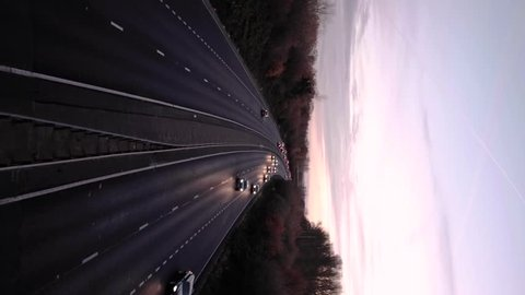 Vertical Video - Cars driving along a motorway at sunset