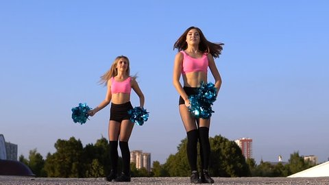 Two girls cheerleaders with pompons dancing outdoors