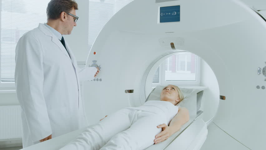 In Medical Laboratory Radiologist Controls MRI or CT or PET Scan with Female Patient Undergoing Procedure. Professional Doctor Conducts Emergency Checkup Procedure with Advanced Medical Technologies. | Shutterstock HD Video #1019002264