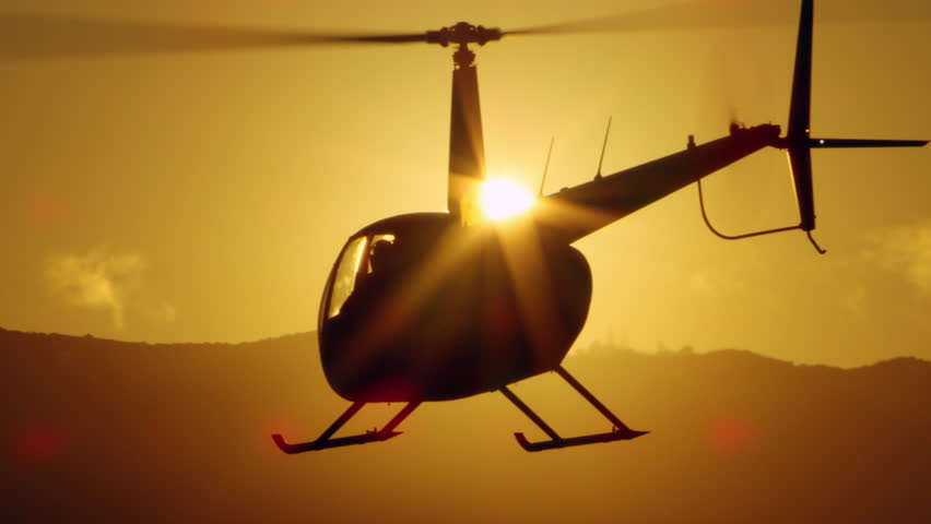 Aerial view of helicopter flying over mountains into the clouds during magical sunset in Los Angeles, California. Wide long shot on 4K RED camera.