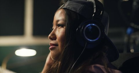 Smooth beats and a smooth shot. A female DJ and sound designer listening to her track in her recording studio using a mixing track. Shot on 8k helium RED.