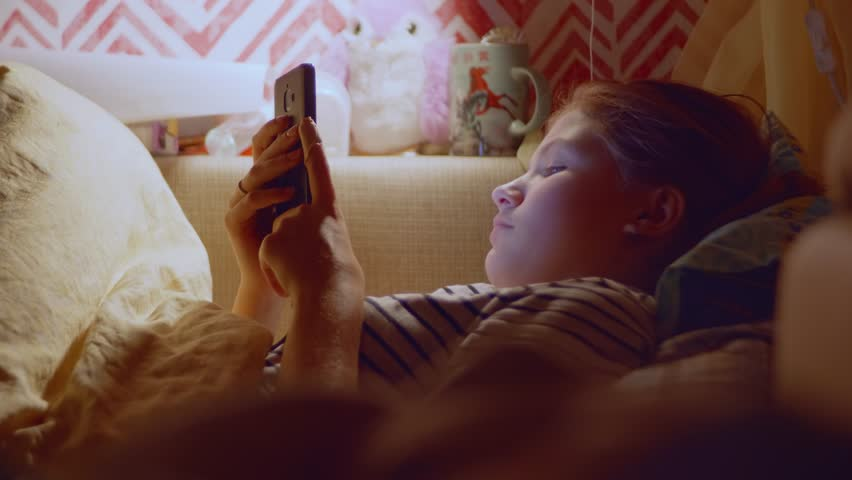 Side view of young blond girl lying in bed with smartphone in hands and surf internet before sleeping | Shutterstock HD Video #1019087194