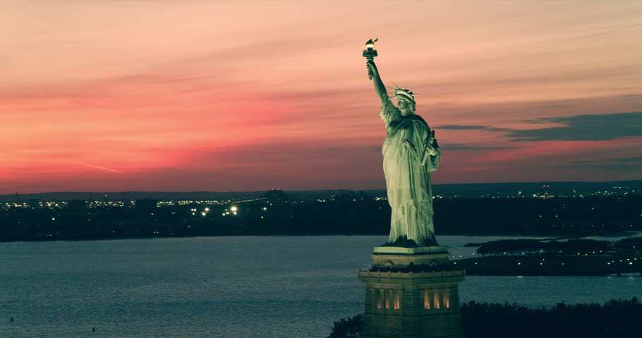 Aerial view of Statue of Liberty in New York under beautiful pink red summer sunset. Wide to Long shot on 4K RED camera. | Shutterstock HD Video #1019092714