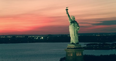 Aerial view of Statue of Liberty in New York under beautiful pink red summer sunset. Wide to Long shot on 4K RED camera.