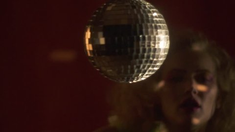 Disco ball spins while a woman in colorful clothes dances on the background