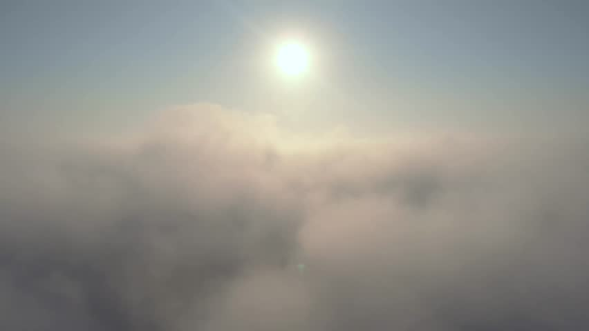 Aerial view over the clouds and sun is shining. Drone flying forward and through while clouds moving. Sun centered above #1019143534