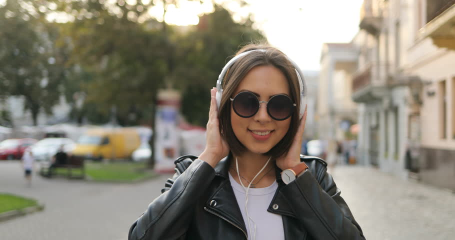 A girl in the headphones is dancing on the street | Shutterstock HD Video #1019169904