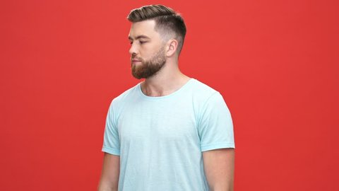 Smiling cool bearded man in t-shirt with crossed arms winks with eye and looking at the camera over red background