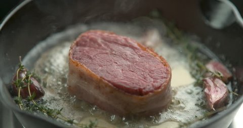 Bacon-wrapped beef tournedos, cooked in butter, garlic and thyme, in a deep frying pan. Close up with shallow depth of field, shot in 4K slow motion with Phantom Flex camera.