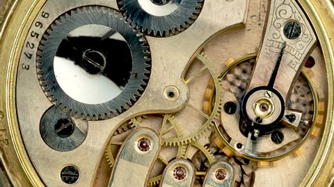 Gears in the mechanism of a vintage pocket watchl. Close up. Time lapse . Back background