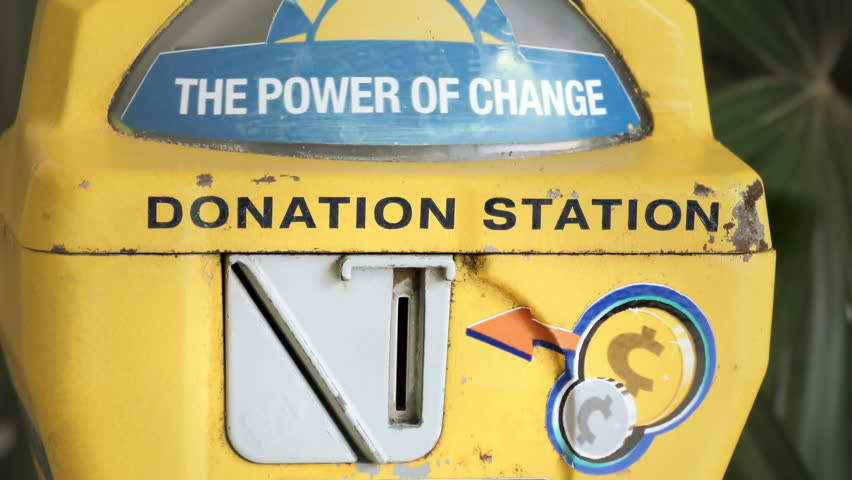 Hand inserting coins into old donation station collection box | Shutterstock HD Video #1019230204