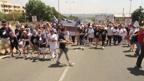 SANDTON, SOUTH AFRICA - MARCH 15 2014 - Global March for Lions Elephants and Rhinos with children chanting behind plastic rhino in the back of a truck