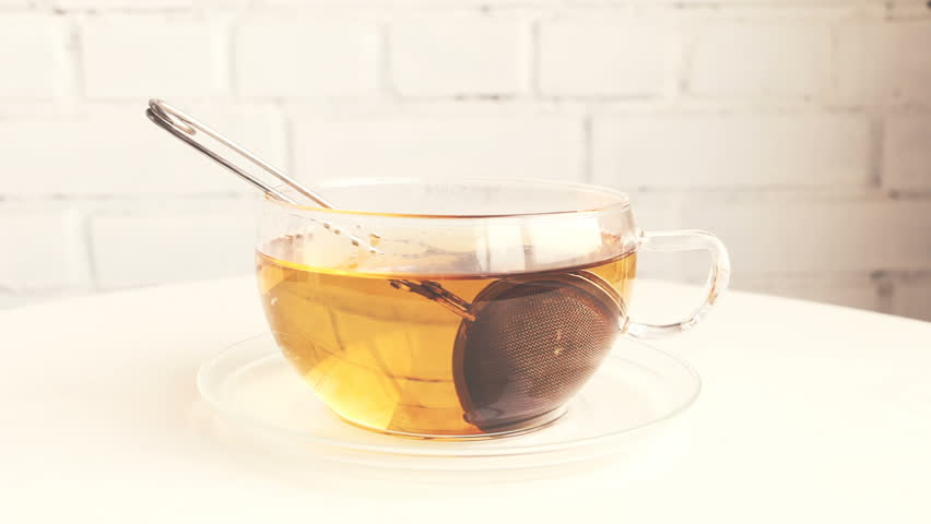 Making tea in transparent glass cup with tea infuser, strainer. Tea changing color. White background. Camera locked down.