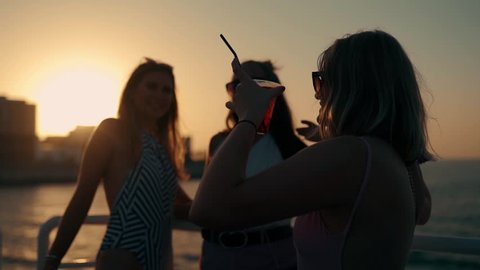 Group of Happy Young girls are Dancing and drinking at the party on the yacht in Sunset Light. Slow Motion