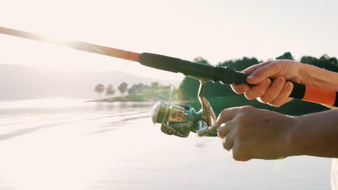 Slow motion slide fragment of rotation of the handle with a reel of fishing rod against the background of orange sunset. A man fishing on a big lake tightens a fishing line a reel of fish. Lens flare